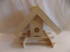 Vogelfutterstelle aus Holz mit Schindeldach und Futterkamin